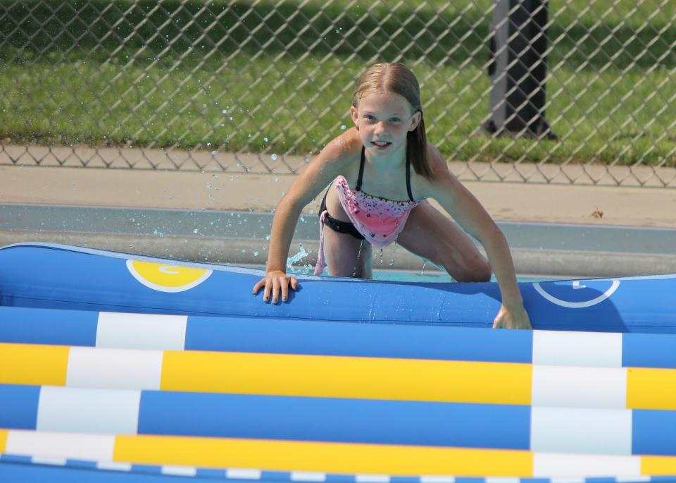 GIrl plays on inflatable pool toys Opens in new window
